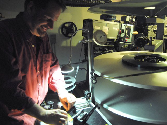The theater owner splicing film.